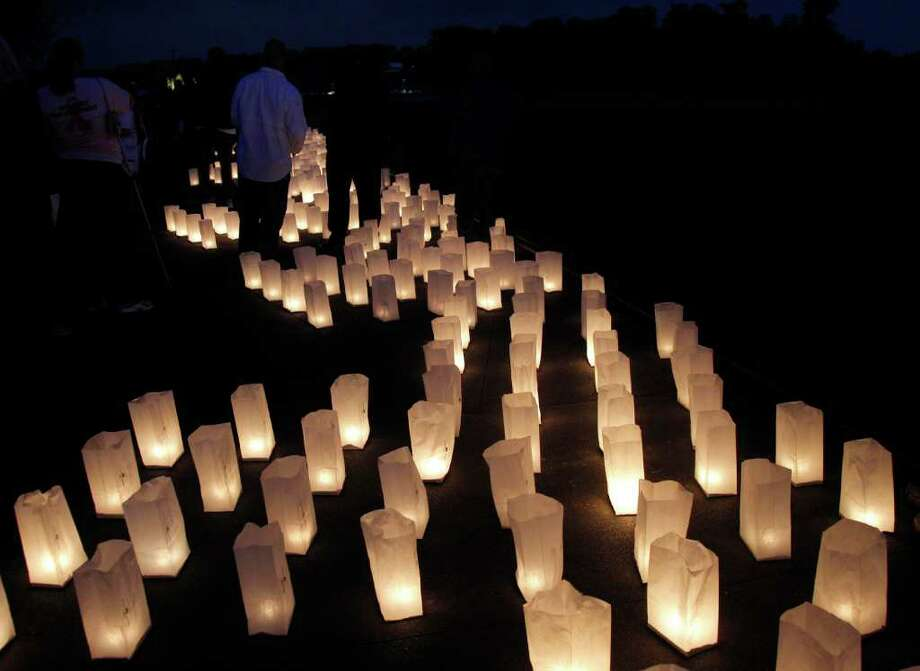 Visitors move amongst candle-lit luminarias at the Wall of Names at phase 1 of the Flight 93 National Memorial near the crash site of Flight 93 in Shanksville, Pa. Saturday Sept. 10, 2011. Photo: AP