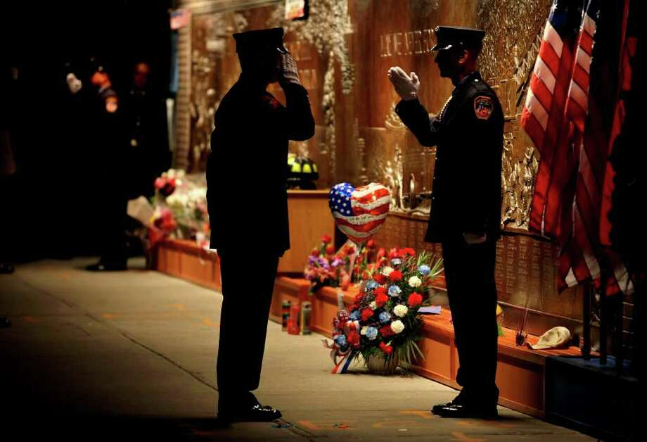 FDNY firefighters stand at a firefighters memorial at the Ten House firehouse Sunday, Sept. 11, 2011 before a ceremony marking the 10th anniversary of the attacks at the World Trade Center. Photo: AP