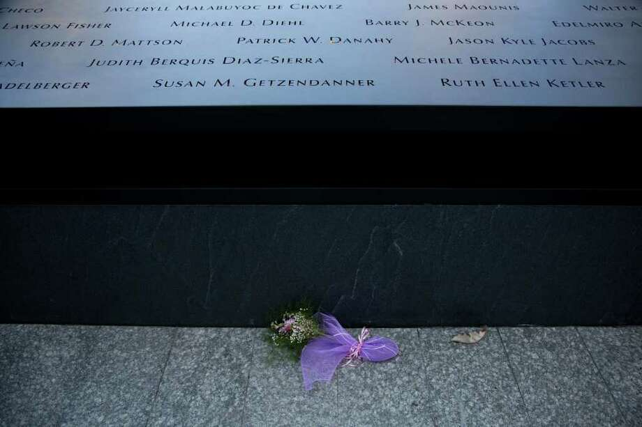 Flowers lay at the base of the south reflecting pool before tenth anniversary ceremonies of the terrorist attacks at the site of the World Trade Center, Sunday, Sept. 11, 2011, in New York. Photo: AP