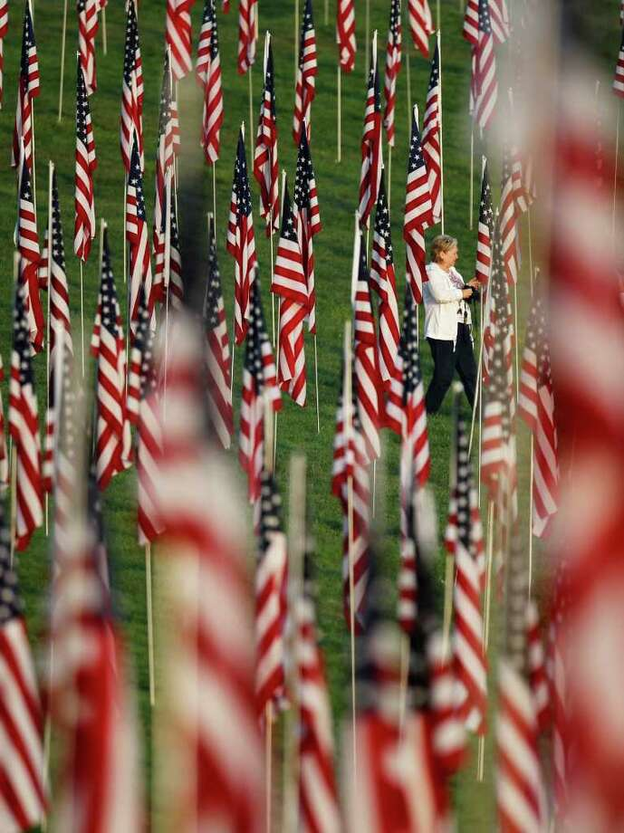 Mary Hauser of Webster Groves, Mo., walks among nearly 3,000 flags set up as part of a remembrance on 10th anniversary of the Sept. 11 terrorist attacks Sunday, Sept. 11, 2011, in St. Louis. Photo: AP