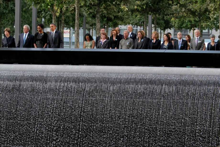President Barack Obama, first lady Michelle Obama, former President George W. Bush, and former first lady Laura Bush, at left from right to left, join family members and others as they observe a moment of silence at the National September 11 Memorial for a ceremony marking the 10th anniversary of the attacks at World Trade Center, Sunday, Sept. 11, 2011 in New York. Photo: AP