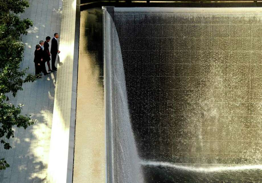 President Barack Obama, right, runs his hand along the names on the Sept. 11 memorial as first lady Michelle Obama, former President George W. Bush, and former first lady Laura Bush look on during a visit to the memorial during the 10th anniversary ceremony at the site of the World Trade Center Sunday, Sept. 11, 2011, in New York. Photo: AP