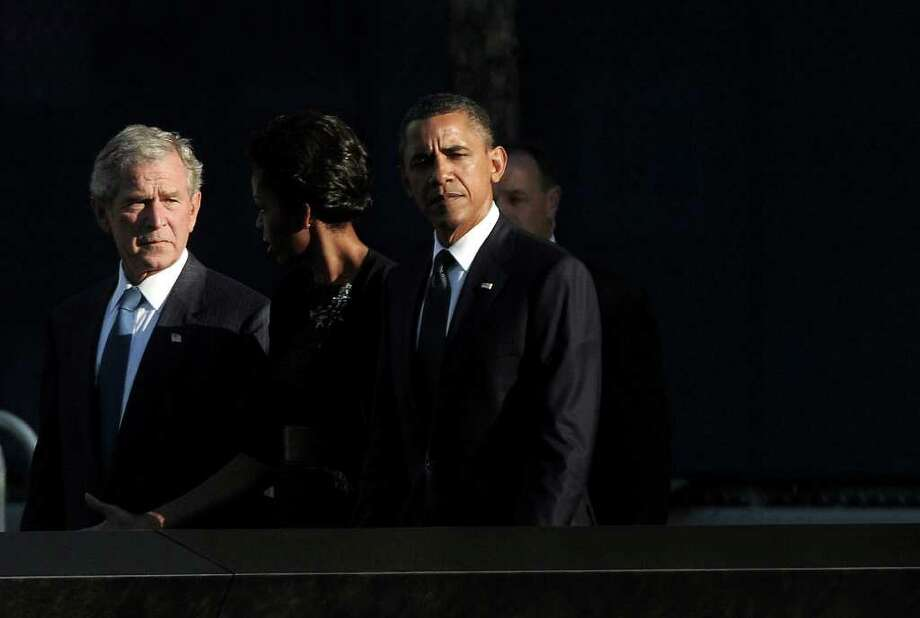 President Barack Obama, right, first lady Michelle Obama, second right, and former President George W. Bush walk past the north pool of the Sept. 11 Memorial during the 10th anniversary ceremony at the site of the World Trade Center in New York, Sunday, Sept. 11, 2011. Photo: AP