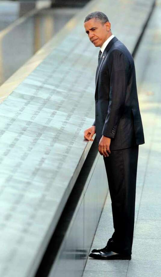 President Barack Obama looks at the names of Sept. 11 victims etched in bronze as he visits the North Memorial Pond at the National Sept. 11th Memorial Sunday, Sept., 11, 2011 in New York. Photo: AP