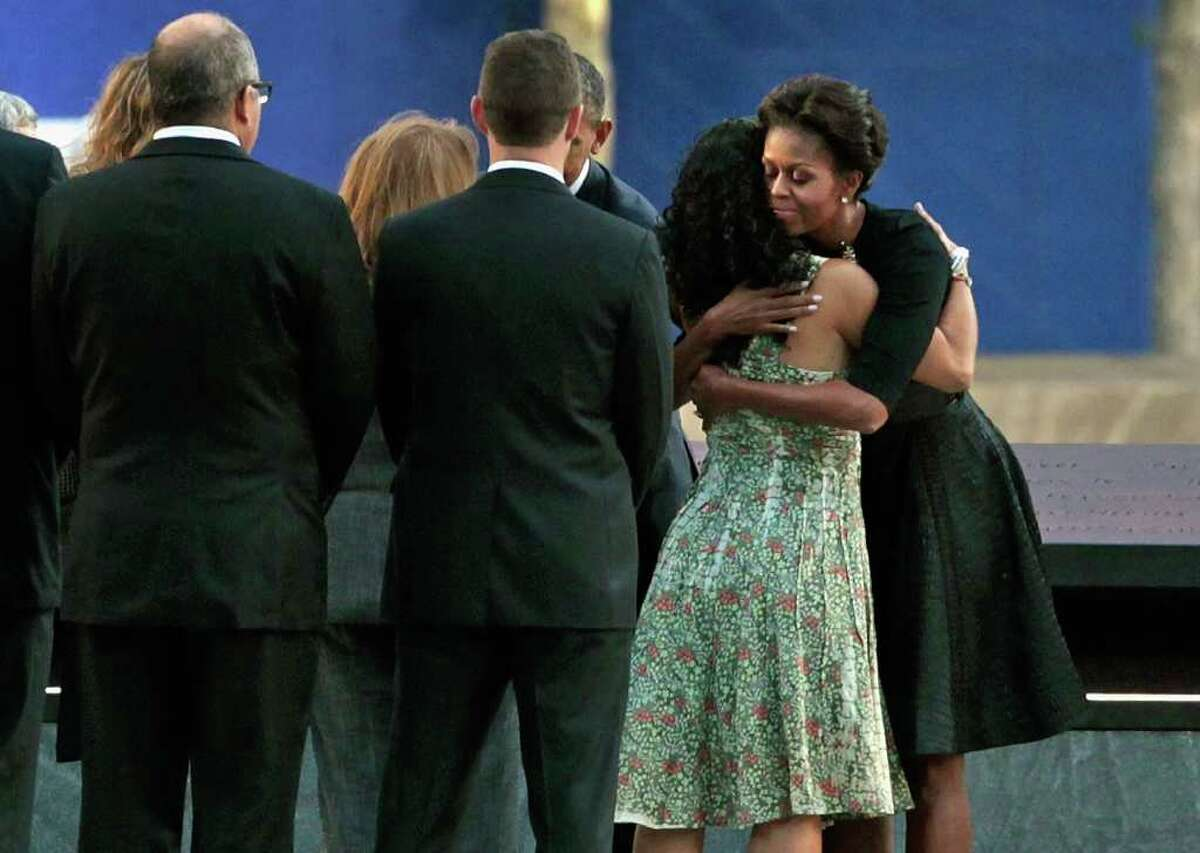 First lady Michelle Obama embraces the family member of a victim of the Sept. 11 terrorist attacks at the Sept. 11 Memorial during the 10th anniversary ceremony at the site of the World Trade Center Sunday, Sept. 11, 2011, in New York.