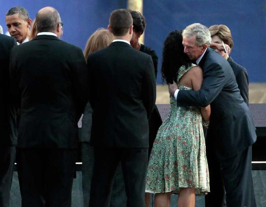 Former President George W. Bush embraces the family member of a victim of the Sept. 11 terrorist attacks at the Sept. 11 Memorial during the 10th anniversary ceremony at the site of the World Trade Center Sunday, Sept. 11, 2011, in New York. Photo: AP