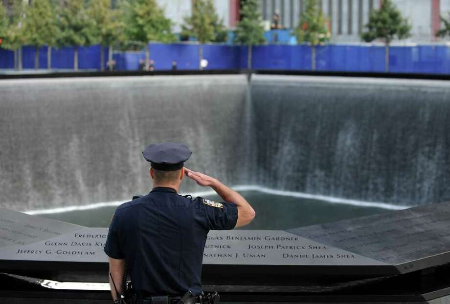 A New York City police officer salutes at the north pool of the Sept. 11 memorial as the national anthem is sung during the 10th anniversary ceremonies at the World Trade Center, Sunday, Sept. 11, 2011, in New York. Photo: AP