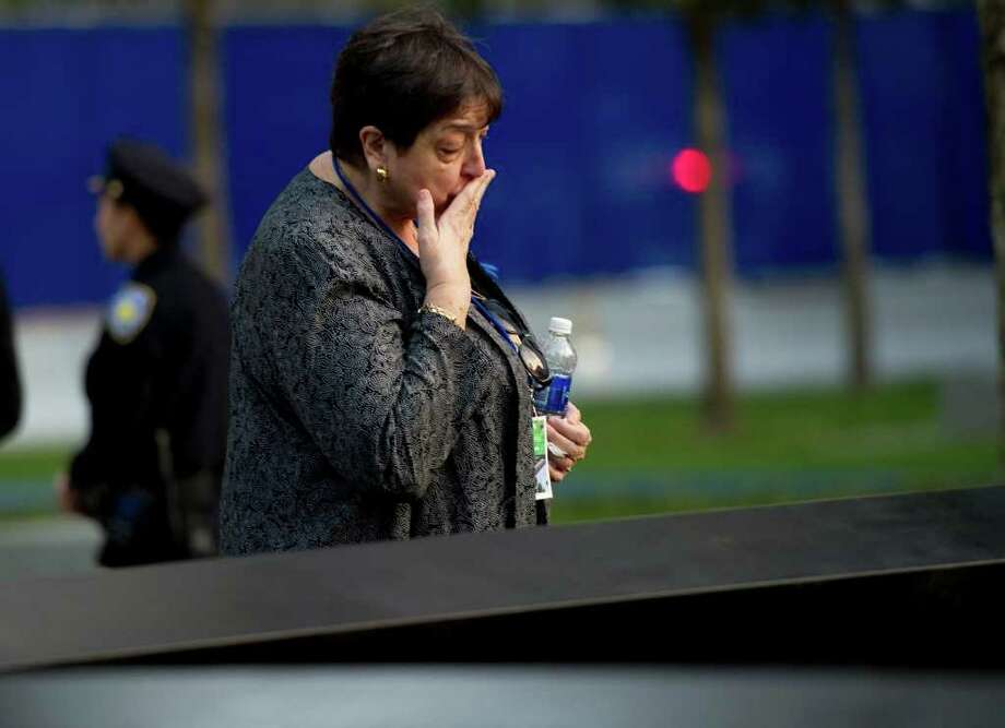A woman kisses the memorial wall on the North Tower reflecting pool of the 9/11 Memorial on September 11, 2011 in New York as the 10th anniversary of the 9/11 attacks is observed. AFP PHOTO/DON EMMERT Photo: DON EMMERT, AFP/Getty Images / 2011 AFP