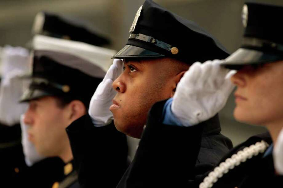 "New York City police and firefighters, and Port Authority of NY & NJ police officers salute during the singing of the ""Star Spangled Banner"" at the Sept. 11 memorial, during 10th anniversary ceremonies at the site, Sunday, Sept. 11, 2011, in New York. Photo: AP"