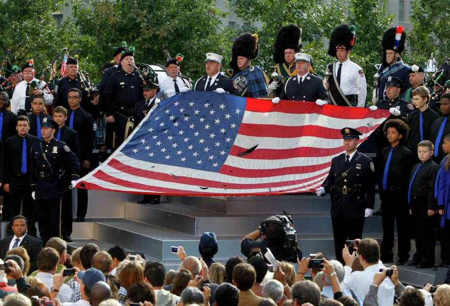 The World Trade Center Flag is presented as friends and relatives of the victims of 9/11 gather for a ceremony marking the 10th anniversary of the attacks at the National September 11 Memorial at the World Trade Center site, Sunday, Sept. 11, 2011, in New York. Photo: AP