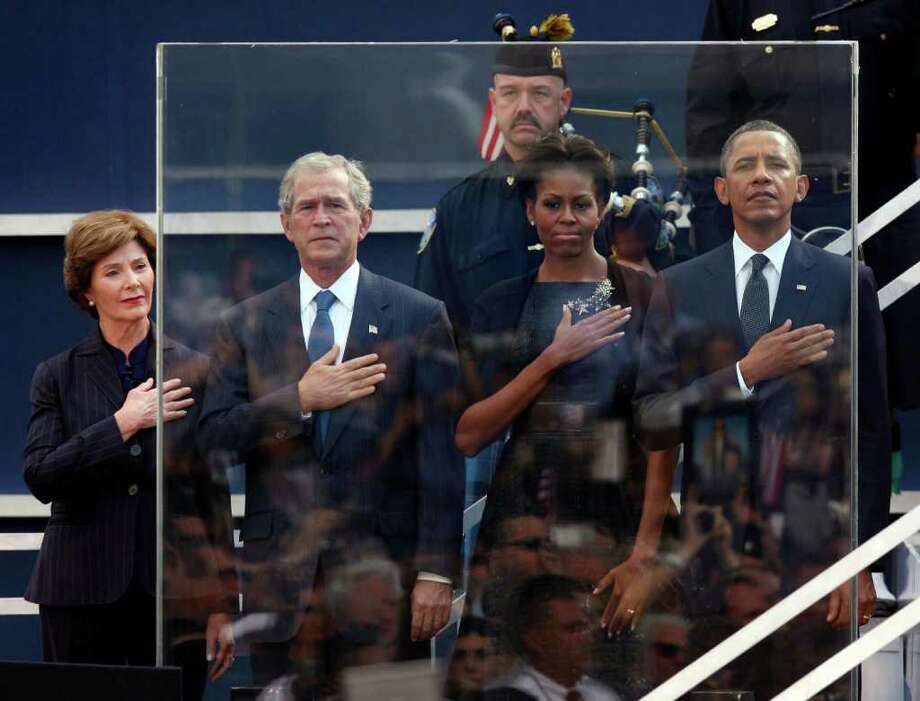Former first lady Laura Bush, from left, former President George W. Bush, first lady Michelle Obama and President Barack Obama hold hands to their hearts during the national anthem as friends and relatives of the victims of 9/11 gather for a ceremony marking the 10th anniversary of the attacks at the National September 11 Memorial at the World Trade Center site, Sunday, Sept. 11, 2011, in New York. Photo: AP