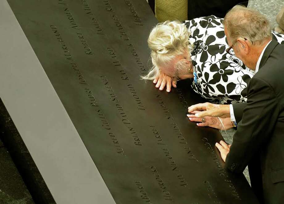 A woman cries over a name on the edge of the south pool at the National September 11 Memorial in New York during the ceremony marking the 10th anniversary of the attacks on the World Trade Center in New York, Sunday, Sept. 11, 2011. Photo: AP