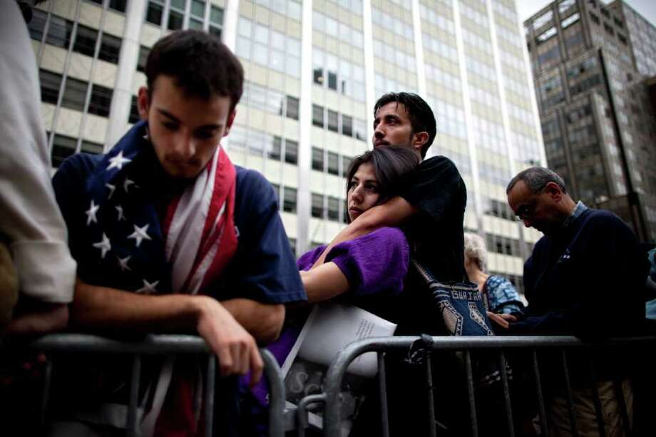 People gather during a ceremony marking the 10th anniversary of the attacks on the World Trade Center Sunday, Sept. 11, 2011, outside the World Trade Center site in New York. Photo: AP