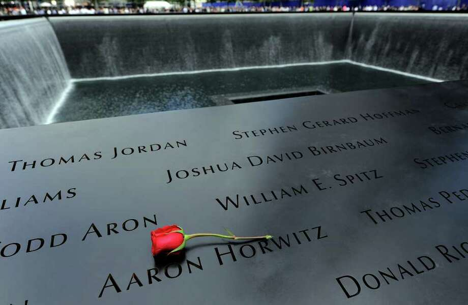 A single rose lies above one of the names inscribed on a wall at the Sept. 11 memorial in New York, Sunday, Sept. 11, 2011, as families who lost loved ones in the World Trade Center attacks joined others to make the 10th anniversary of those attacks. Photo: AP