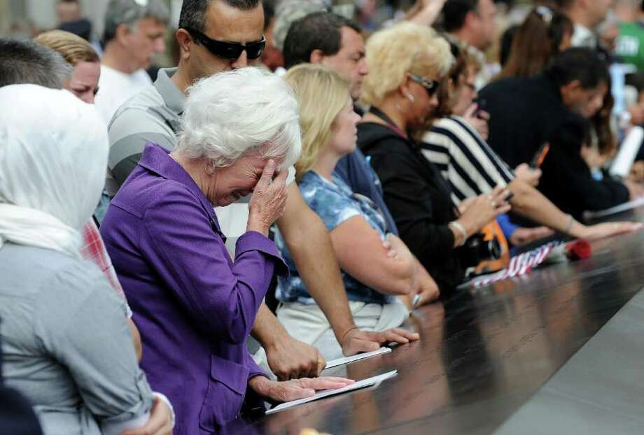 A woman cries over a name inscribed on the edge of the north pool at the National September 11 Memorial in New York during the ceremony marking the 10th anniversary of the attacks on the World Trade Center, Sunday, Sept. 11, 2011. Photo: AP