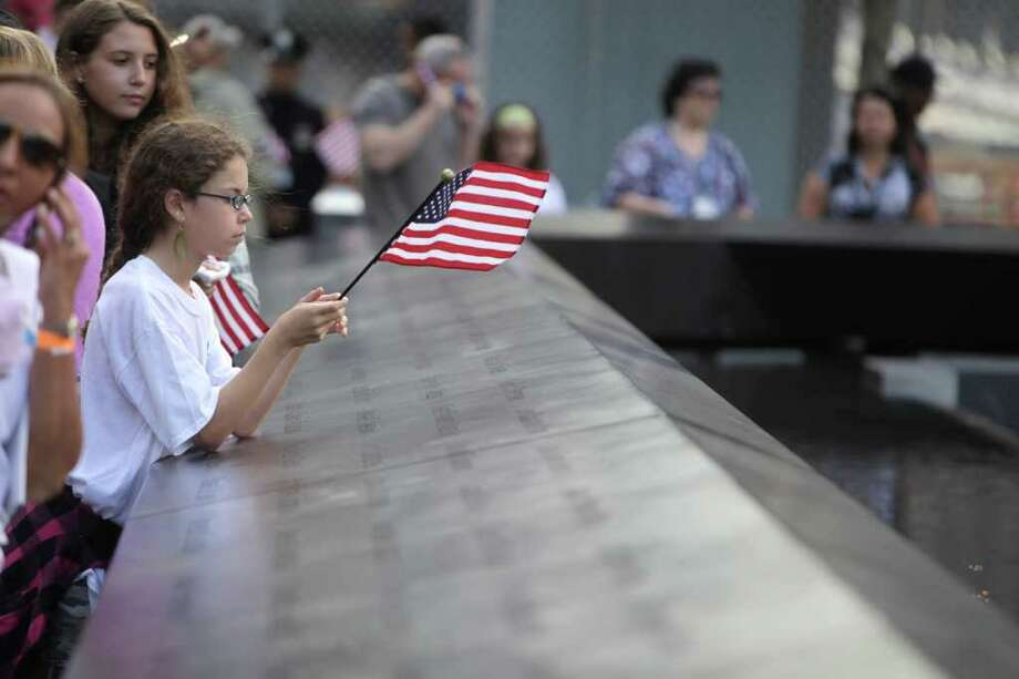 Eliza Peterson holds a flag near the name of her uncle, Norman Rossinow, who was killed Sept. 11, 2001 terrorist attacks, at the Sept. 11 memorial at the World Trade Center site in New York, Sunday, Sept. 11, 2011. Photo: AP