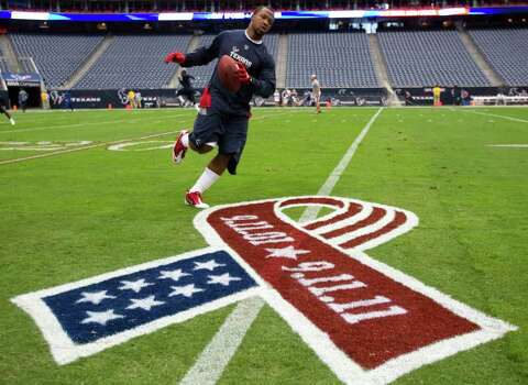 Houston Texans defensive back Glover Quin runs past a 9-11 commemorative logo as he warms up before an NFL football game against the Indianapolis Colts at Reliant Stadium Sunday, Sept. 11, 2011, in Houston. Photo: Brett Coomer, Houston Chronicle / © 2011 Houston Chronicle