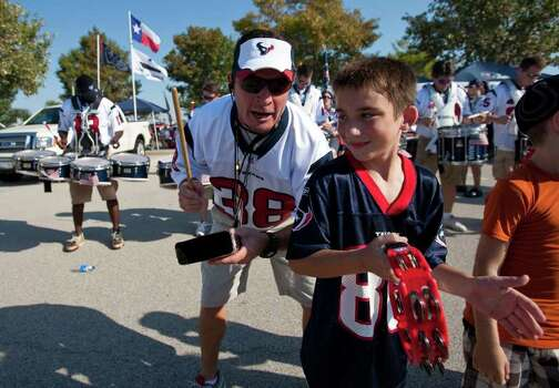 Lamar Burkhalter, left, of the Houston Texans Bull Pen Pep Band, plays with Blake Seele, 9, of Houston, as the band entertains tailgaters before the Houston Texans' season opening game against the Indianapolis Colts, Sunday, Sept. 11, 2011, in Reliant Stadium in Houston. Photo: Nick De La Torre, Houston Chronicle / © 2011 Houston Chronicle
