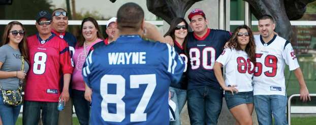 Lee Valdez, of Alamo, Texas, wearing a Reggie Wayne jersey, takes a picture of Simon Palafox, wearing a blue Andre Johnson jersey, and his family before the Houston Texans' season opening game against the Indianapolis Colts, Sunday, Sept. 11, 2011, in Reliant Stadium in Houston. Photo: Nick De La Torre, Houston Chronicle / © 2011 Houston Chronicle