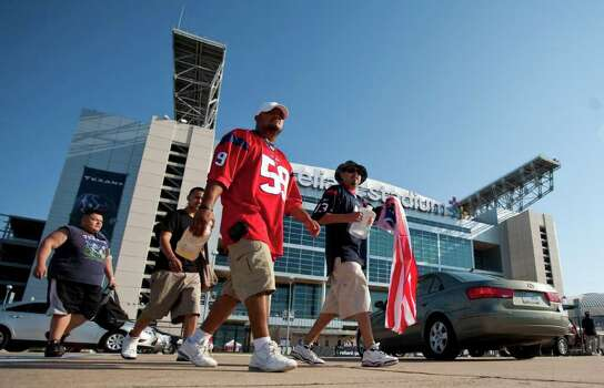 Steve Silva, front, of Houston, walks with his friend Gabriel Aguilar, retired U.S.M.C., back right, walk into the parking lot to meet friends before the Houston Texans' season opening game against the Indianapolis Colts, Sunday, Sept. 11, 2011, in Reliant Stadium in Houston. Photo: Nick De La Torre, Houston Chronicle / © 2011 Houston Chronicle