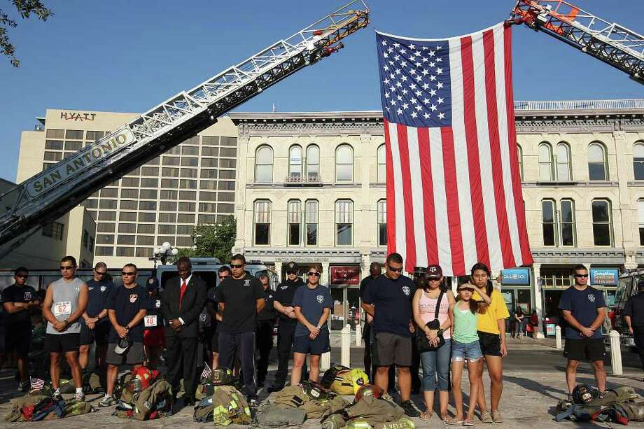 Members of the San Antonio Fire Department, family and friends stand by the U.S. flag during the City of San Antonio commemoration of the 10th anniversary of the September 11 attack on the U.S. at Alamo Plaza, Sunday, Sept. 11, 2011. Photo: JERRY LARA, JERRY LARA/glara@express-news.net / SAN ANTONIO EXPRESS-NEWS