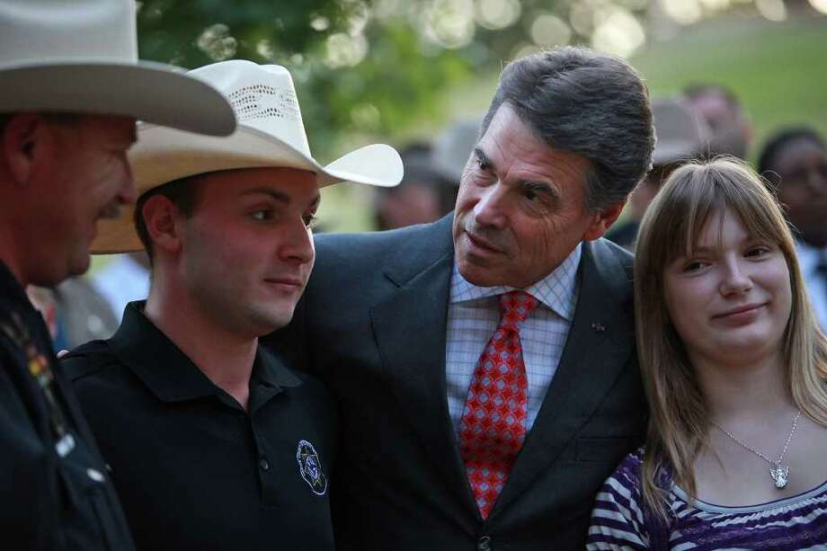 Gov. Rick Perry talks with Bob Goerlitz, president of the Harris County Deputies' Organization, and his children, Michelle Goerlitz, 13, and James Goerlitz, 20, after Perry led a Memorial Service at the 9/11 Monument, which features two steel columns from ground zero, at the Texas State Cemetery in Austin on Sunday, Sept. 11, 2011. Photo: LISA KRANTZ, LISA KRANTZ/lkrantz@express-news.net / SAN ANTONIO EXPRESS-NEWS