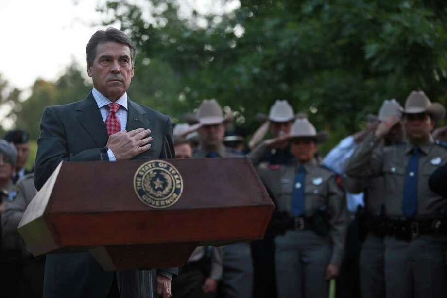Governor Rick Perry stands as the colors are posted during a Memorial Service for the September 11 attacks in front of the 9/11 Monument at the Texas State Cemetery in Austin on Sunday, Sept. 11, 2011. Photo: LISA KRANTZ, LISA KRANTZ/lkrantz@express-news.net / SAN ANTONIO EXPRESS-NEWS