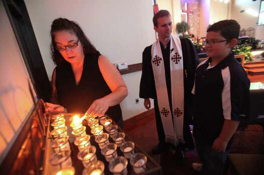 Elena Collins, 41, lights a candle while Rev. Josh Hubert and Cody Collins, 11, wait their turn during Sunday Service at Wildwood United Methodist Church as it observes the Sept. 11th attacks anniversary and pray for fire victims in the tri-county wildfires on Sunday, Sept. 11, 2011, in Magnolia. Photo: Mayra Beltran, Houston Chronicle / © 2011 Houston Chronicle