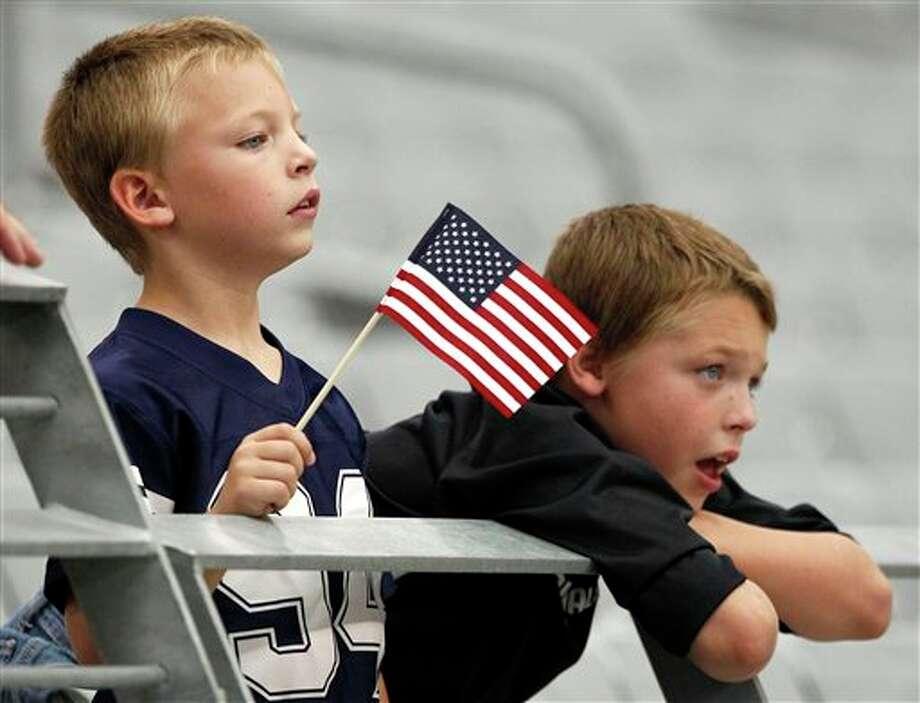 Keegan Landis, 6, left, and his brother John Landis, 9, watch the Arizona Cardinals and the Carolina Panthers warm up prior to an NFL football game, Sunday, Sept. 11, 2011, in Glendale, Ariz. (AP Photo/Matt York) Photo: Associated Press