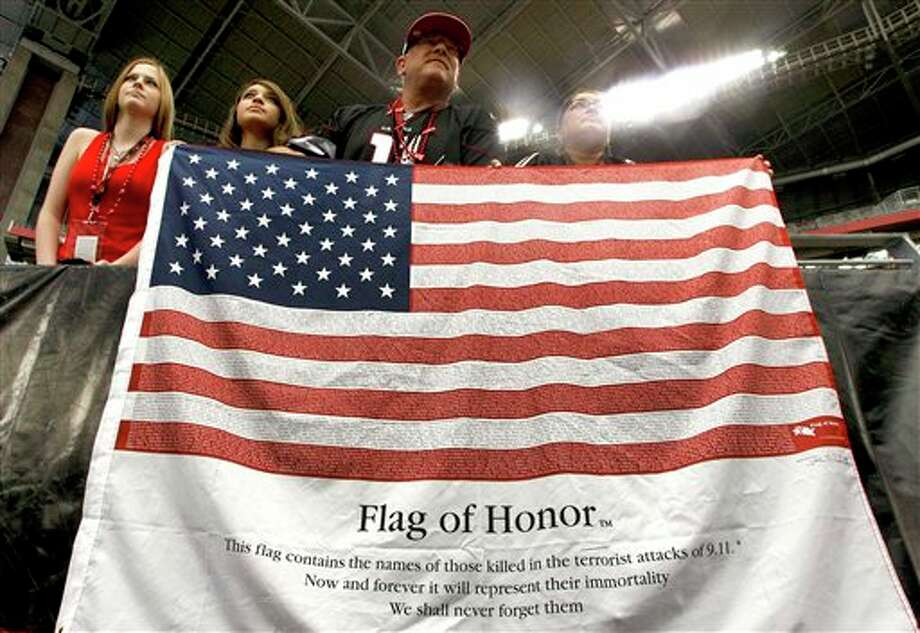 Joel Soderburg, third from left, daughter Marissa Soderburg, 17, left, daughter  Delores Soderburg, second from left , and daughter Jessica Soderburg, 17,  right, hang a flag with the names of those lost 10 years ago before an NFL football game between the Arizona Cardinals and the Carolina Panthers, Sunday, Sept. 11, 2011, in Glendale, Ariz. (AP Photo/Ralph Freso) Photo: Associated Press