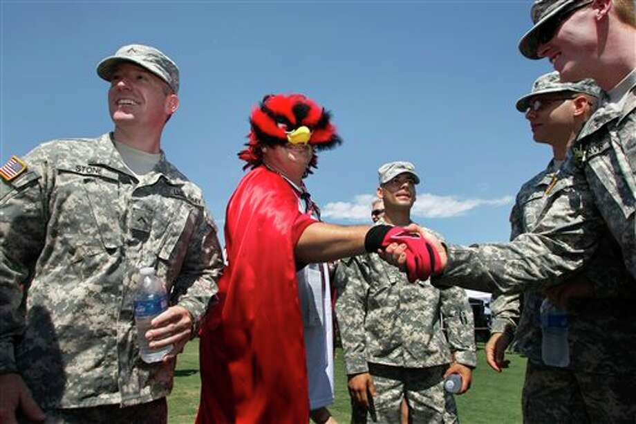 Troy Escobedo, center, greets U.S. Army soldier Nick Stone prior to an NFL football game between the Arizona Cardinals and the Carolina Panthers, Sunday, Sept. 11, 2011, in Glendale, Ariz. (AP Photo/Ralph Freso) Photo: Associated Press