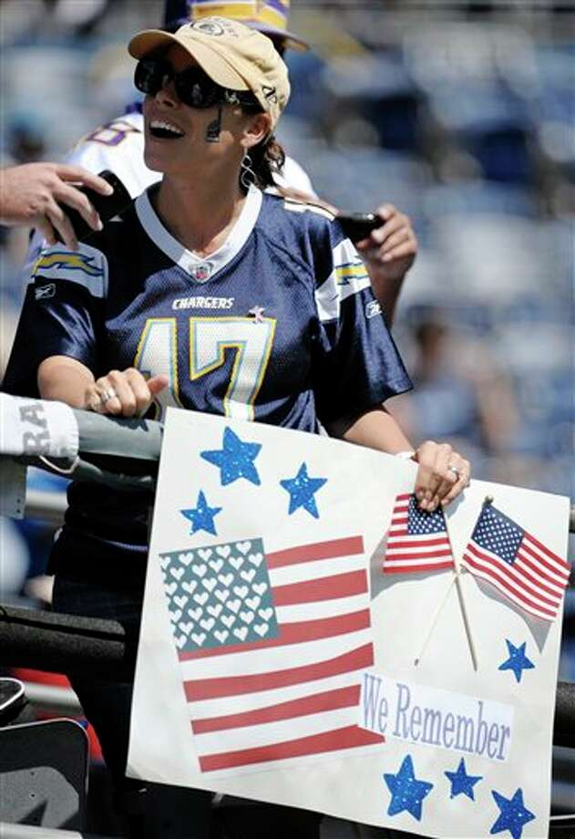 A San Diego Chargers fan holds a sign commemorating the attacks of Sept. 11, 2001, before an NFL football game between the Chargers and the Minnesota Vikings on Sunday, Sept. 11, 2011, in San Diego. (AP Photo/Denis Poroy) Photo: Associated Press