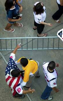 Houston Texans fan wearing an American flag is patted down by security before an NFL football game against the Indianapolis Colts at Reliant Stadium on Sunday, Sept. 11, 2011, in Houston. Photo: Smiley N. Pool, Houston Chronicle / © 2011  Houston Chronicle
