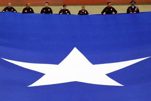 Law enforcement personnel display a large Texas flag before an NFL football game against the Indianapolis Colts at Reliant Stadium on Sunday, Sept. 11, 2011, in Houston. Photo: Smiley N. Pool, Houston Chronicle / © 2011  Houston Chronicle