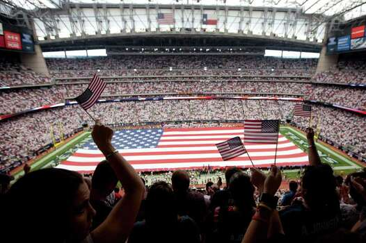 Houston Texans fans wave flags as large American flag is unfurled on the field before an NFL football game against the Indianapolis Colts at Reliant Stadium on Sunday, Sept. 11, 2011, in Houston. Photo: Smiley N. Pool, Houston Chronicle / © 2011  Houston Chronicle