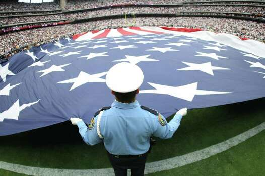 A large American flag is unfurled across the field before a NFL game, between the Houston Texans and Indianapolis Colts, Sunday, Sept. 11, 2011, at Reliant Stadium in Houston. Photo: Nick De La Torre, Houston Chronicle / © 2011 Houston Chronicle