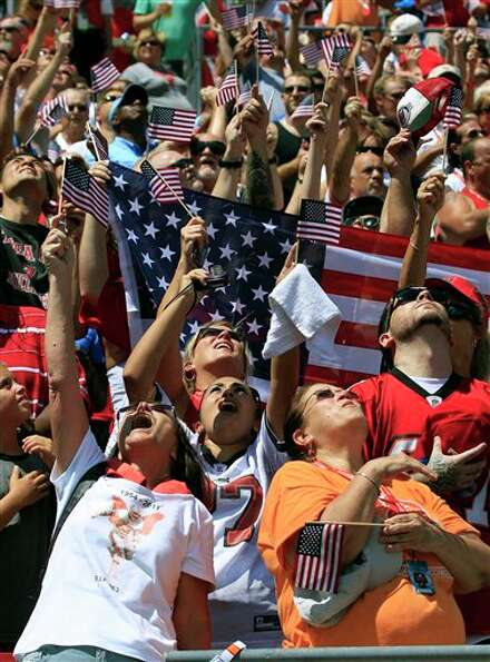 Tampa Bay Buccaneers fans react as a military flyover proceded over the stadium at the conclusion of