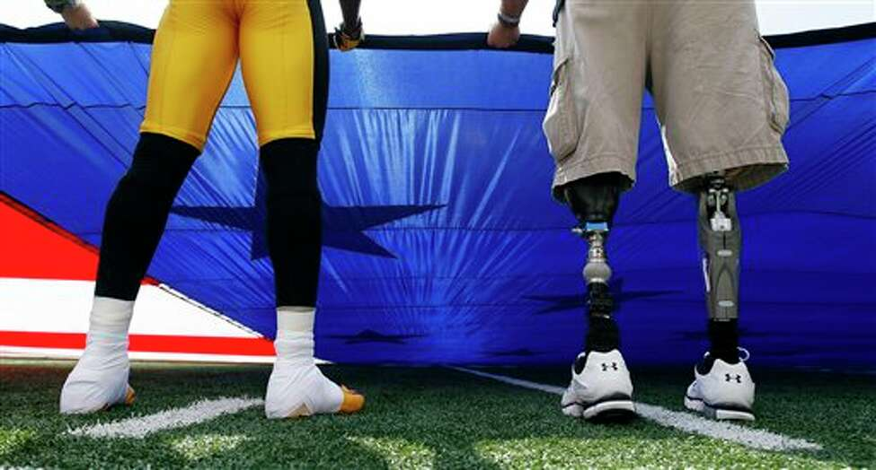 Pittsburgh Steelers defensive back William Gay, left, holds an American flag next to Mike Martinez, who lost his legs while serving with the U.S. Marines in Afghanistan, before an NFL football game against the Baltimore Ravens, Sunday, Sept. 11, 2011, in Baltimore. Today marks the 10th anniversary of the 9/11 attacks. (AP Photo/Patrick Semansky)