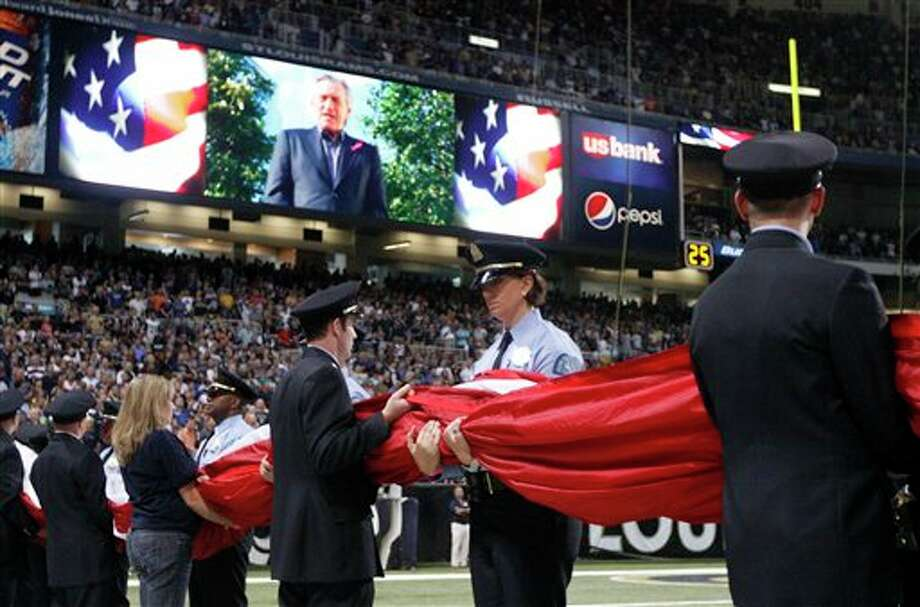St. Louis police and firefighters hold a large flag as Robert DeNiro is seen on a video board in a pregame ceremony in honor of the 10th anniversary of the Sept. 11 terrorist attacks before the start of an NFL football game between the St. Louis Rams and the Philadelphia Eagles Sunday, Sept. 11, 2011 in St. Louis. (AP Photo/Jeff Roberson) Photo: Associated Press