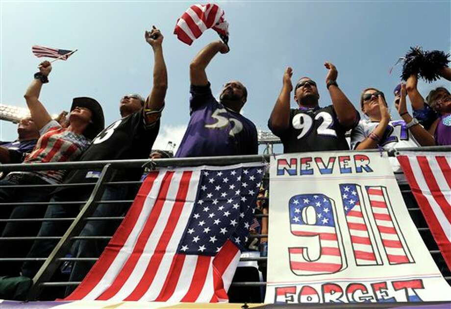 Fans cheer in front of signs and flags honoring the tenth anniversary of the Sept. 11, 2001, terrorist attacks before an NFL football game between the Baltimore Ravens and the Pittsburgh Steelers in Baltimore, Sunday, Sept. 11, 2011. (AP Photo/Gail Burton) Photo: Associated Press
