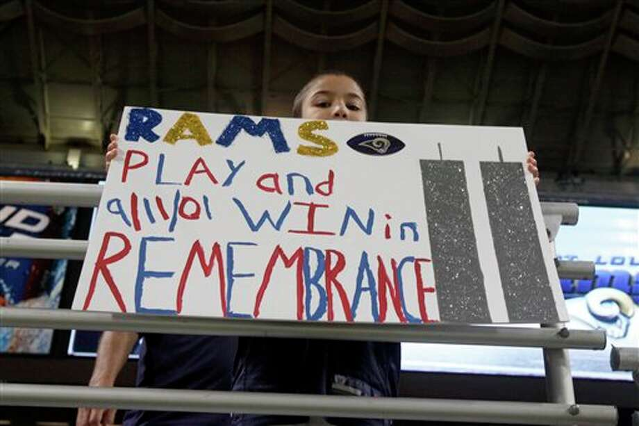 A young fan hold up a sign in honor of the 10th anniversary of the Sept. 11 terrorist attacks before the start of an NFL football game between the St. Louis Rams and the Philadelphia Eagles Sunday, Sept. 11, 2011 in St. Louis. (AP Photo/Jeff Roberson) Photo: Associated Press