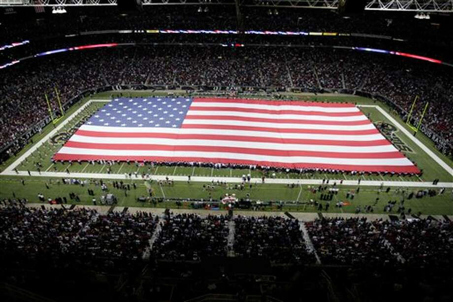 A flag covers the field in honor of the 10th anniversary of the Sept. 11 terrorist attacks, before the start of an NFL football game between the St. Louis Rams and the Philadelphia Eagles Sunday, Sept. 11, 2011 in St. Louis. (AP Photo/Tom Gannam) Photo: Associated Press