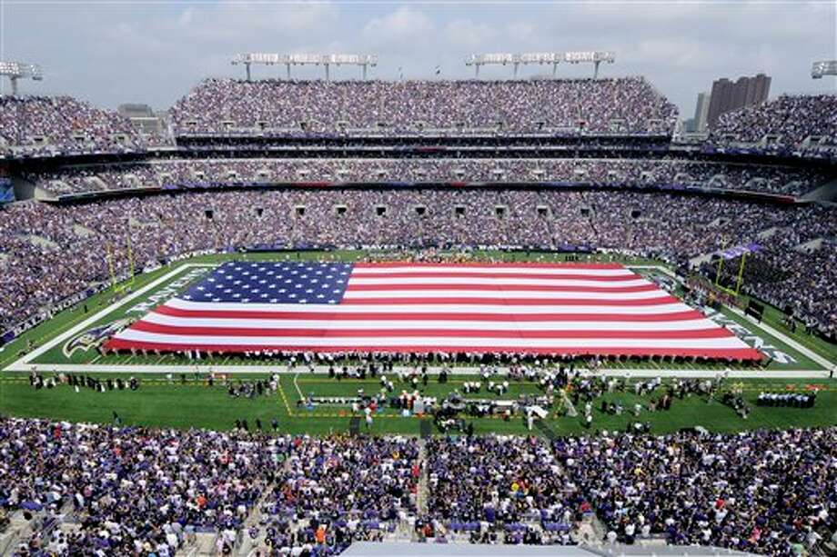 An American flag is unfurled onto the field at M&T Bank Stadium to honor the 10 year anniversary of the Sept. 11, 2001,  attacks before an NFL football game between the Baltimore Ravens and the Pittsburgh Steelers, Sunday, Sept. 11, 2011, in Baltimore. (AP Photo/Nick Wass) Photo: Associated Press