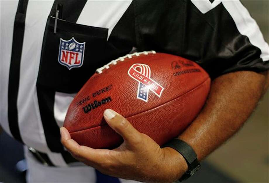 Referee Don Carey holds a ceremonial game ball on the 10th anniversary of the Sept. 11 attacks before an NFL football game between the Chicago Bears and the Atlanta Falcons in Chicago, Sunday, Sept. 11, 2011. (AP Photo/Charles Rex Arbogast) Photo: Associated Press