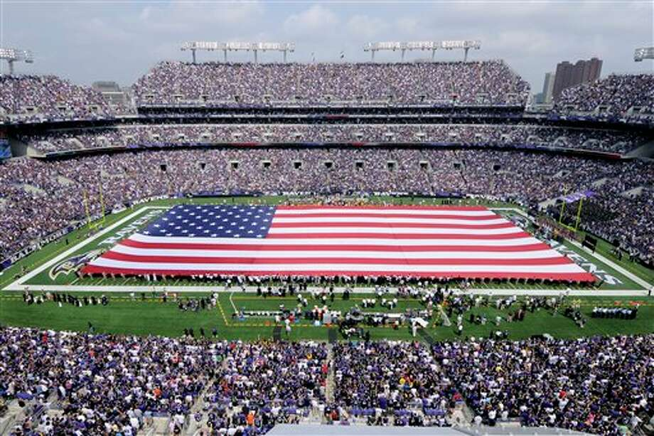 An American flag is unfurled onto the field at M&T Bank Stadium to honor the ten year anniversary of the Sept. 11, 2001, terrorist attacks before an NFL football game between the Baltimore Ravens and the Pittsburgh Steelers in Baltimore, Sunday, Sept. 11, 2011. (AP Photo/Nick Wass) Photo: Associated Press