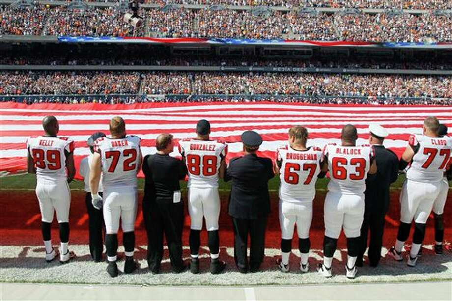 Atlanta Falcons players along with firefighters and police officers hold a giant American flag on the field observing the 10th anniversary of the Sept. 11 attacks before an NFL football game between the Falcons and Chicago Bears, Sunday, Sept. 11, 2011,  in Chicago. (AP Photo/Charles Rex Arbogast) Photo: Associated Press