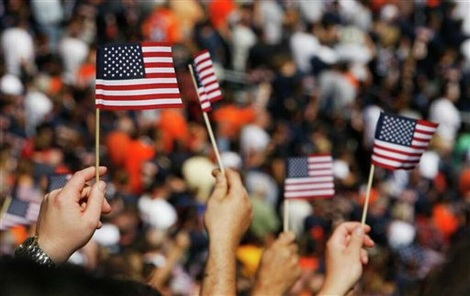 Fans wave United States flags before an NFL football game between the Chicago Bears and the Atlanta Falcons in Chicago, Sunday, Sept. 11, 2011. The day marks the 10th anniversary of the Sept. 11 attacks. (AP Photo/Kiichiro Sato) Photo: Associated Press