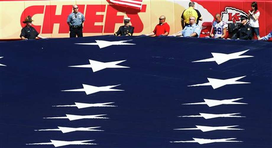 First responders and a Buffalo Bills player hold an American flag before an NFL football game between the Buffalo Bills and Kansas City Chiefs at Arrowhead Stadium in Kansas City, Mo., Sunday, Sept. 11, 2011. (AP Photo/Orlin Wagner) Photo: Associated Press
