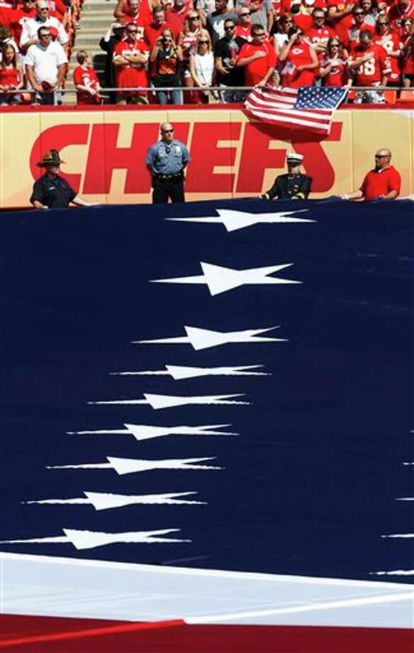 First responders hold an American flag before an NFL football game between the Buffalo Bills and Kansas City Chiefs at Arrowhead Stadium, Sunday, Sept. 11, 2011, in Kansas City, Mo. The day marks the 10th anniversary of the 9/11 attacks. (AP Photo/Orlin Wagner) Photo: Associated Press