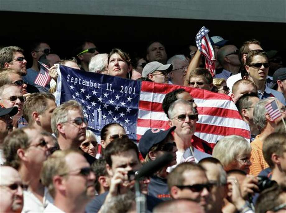 Fans hold a commemorative flag at Soldier Field before an NFL football game between the Chicago Bears and the Atlanta Falcons in Chicago, Sunday, Sept. 11, 2011. The day marks the 10th anniversary of the Sept. 11 terrorist attacks. (AP Photo/Nam Y. Huh) Photo: Associated Press